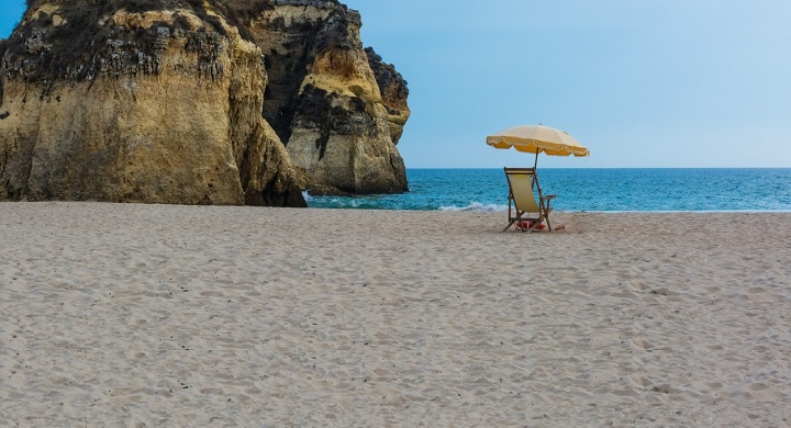 deckchair-and-beach-umbrella-near-rock-on-beach.jpg